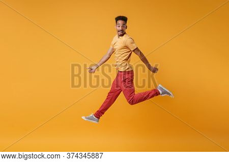 Side View Of Excited Young African American Guy In Casual Clothes Posing Isolated On Yellow Orange B