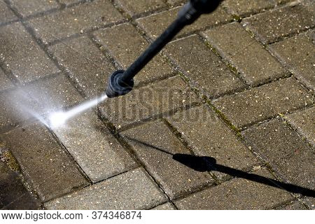 High-pressure Washer Cleans Concrete Stones Of Garden Line In Country House. Spring Cleaning Concept