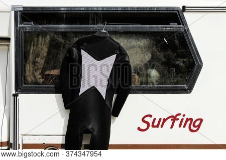 Surfing Suit Hanging On The Side Of A Vintage Caravan - Camper Of Surfer With A Surfing Suit On Clot