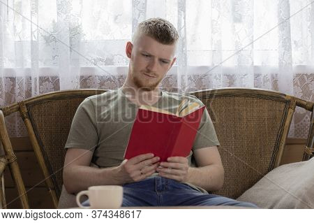 Young Man Concentrated At Reading Book With Red Cover On Wicker Bench In Countryside Wooden House. F