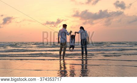 Family Concept. Father And Mother Swing Their Daughter By The Sea. 4k Resolution.