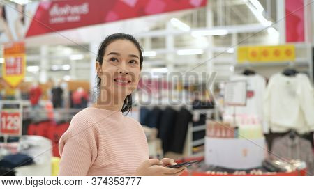 Shopping Concept. An Asian Woman Is Playing A Mobile Phone In A Mall. 4k Resolution.