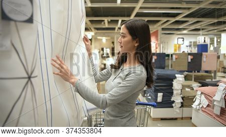 Shopping Concept. An Asian Woman Is Buying Curtains In A Mall. 4k Resolution.