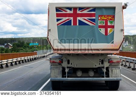 Big  Truck With The National Flag Of  Fiji  Moving On The Highway, Against The Background Of The Vil