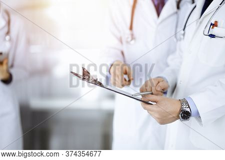 Unknown Doctors, Two Men And A Woman, Discuss Medical Exam Resoults, While Standing At Sunny Hospita