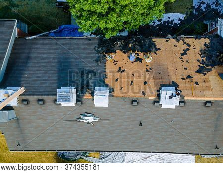 Roofer At Work Repairing A Has Been Removal Of Old Shingle Roof Damaged And Needing Replacement