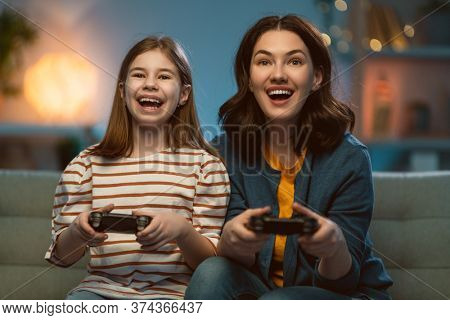 Happy family together. Mother and her child girl playing video games. People having fun at home.