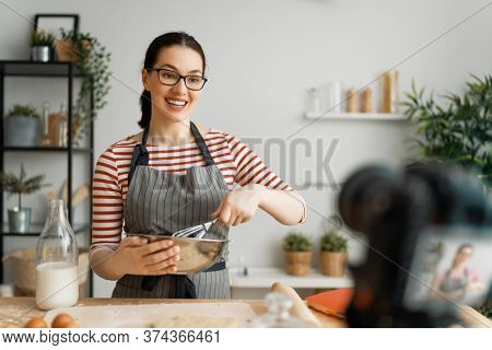 Young confident woman is talking on digital camera recording vlog about cooking.