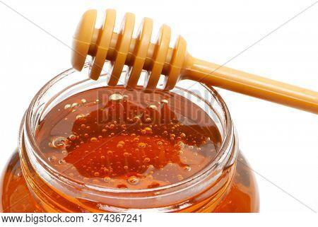 golden bee honey in a glass jar and honey dipper