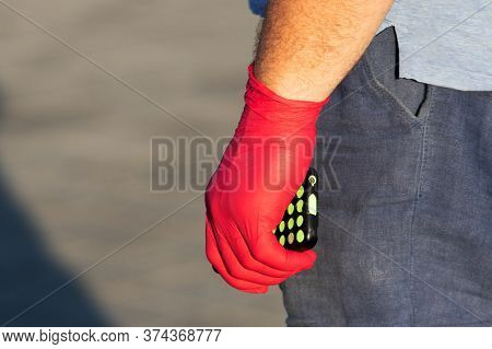 Male Hand In A Red Disposable Glove Holds A Smartphone