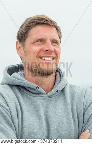 Close-up Portrait Of A Charming Smiling Man In A Gray Hoodie Who Admires Nature And Walking Along Th