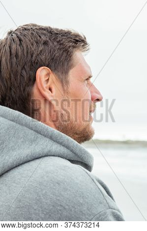 Profile Of A Handsome Man In A Gray Hoodie Who Admires Nature And Walking Along The Beach