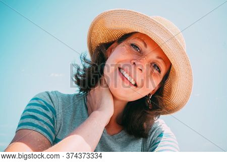 Portrait Of A Beautiful Young Brunette Woman In A Straw Hat On A Background Of Blue Sky On A Sunny D