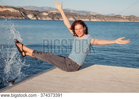 Happy Young Woman Sitting On A Pier On A Lake And Having Fun With Water. Girl Splashes Water On The