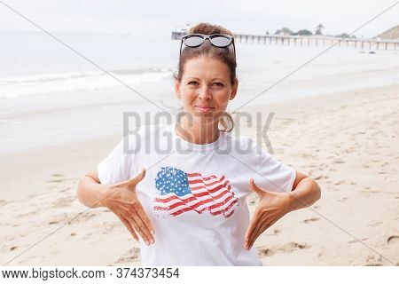 Beautiful Young Woman In A White T-shirt With The American Flag Walking Along The Sandy Beach On A S