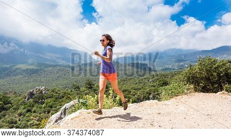 A Woman Runs Along A Mountain Trail, Runner Is Training In The Mountains, Girl Jogging In The Park,