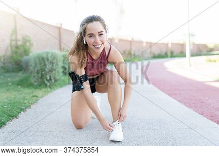 Smiling Attractive Young Woman Tying Shoelace On Footpath While Exercising In Park