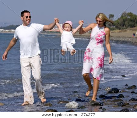 Young Family Playing With Daughter On Beach In Spain