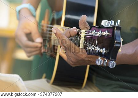 Closeup Of Man's Hand Playing Acoustic Guitar, Soft Vintage Style.
