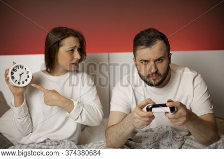 Young Couple Quarrel In Bedroom Due To Gambling Addiction. Handsome Excited Man With Joysticks In Ha