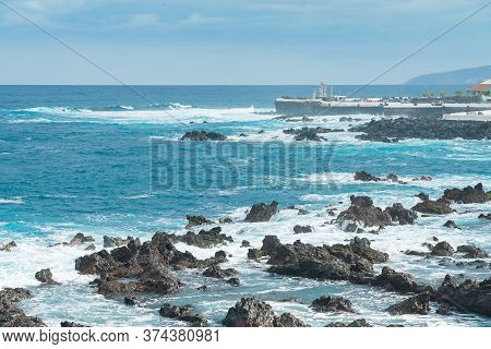 Rocky Shore Of Puerto De La Cruz. Waves Of Atlantic Ocean Roll Over The Rocks On A Sunny Day, Teneri
