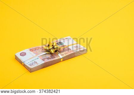 On A Yellow Background Lies A Bundle Of Notes With A Yellow Ribbon And A Bow