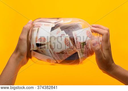 Hands Holding A Three-liter Jar In Which Lie Five Thousandth Bills, Yellow Background