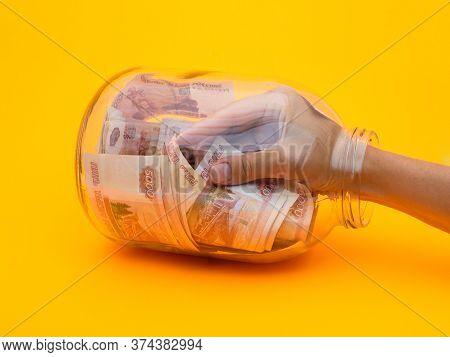 Hand Climbed Into A Glass Jar Full Of Five Thousandth Bills