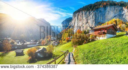 Gorgeous Autumn Landscape Of  Alpine Village Lauterbrunnen With Famous Church And Staubbach Waterfal