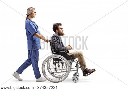 Full length profile shot of a female nurse pushing a disabled man in a wheelchair isolated on white background