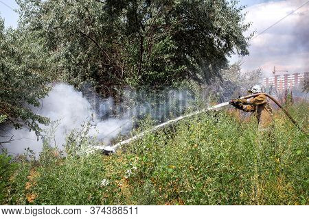 Fireman In A Protective Suit With A Hose Pours Water Under Burning Pressure Burning Garbage In A Nat