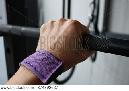 Woman's Hand Gripping A Barbell At The Gym. Fitness, Exercise And Gym Motivation Concept
