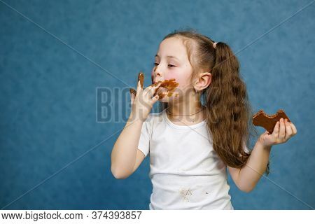 Little Girl Eats Chocolate And Smudges Her White T-shirt, Face And Hands Him