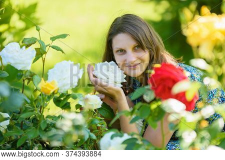 Portrait Of A Smiling Girl Against The Backdrop Of Roses In The Park
