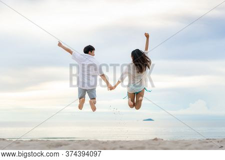Happy Asian Couple Tourists Jumping On Beach Vacations. Travel Concept Of Young Couple Cheering For