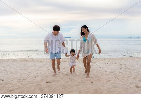 Happy Asian Family Holidays During Joyful Father, Mother And Daughter Running Together Along Summer