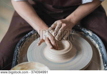 Close-up View Of Woman Hands Working On Pottery Wheel And Making Clay Pot. Hands Sculpts A Cup From