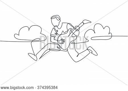 Single Line Drawing Of Young Energetic Guitarist Jumping At Stage And Playing His Electric Guitar. E