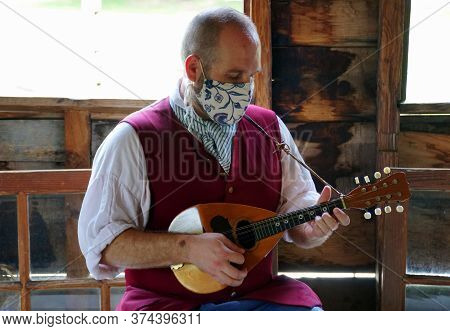 A Williamsburg, Virginia, U.s.a - June 30, 2020 - A Man Playing A Guitar Wearing A Mask As Required