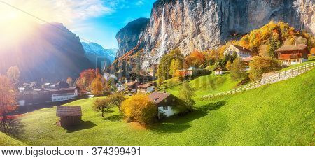 Stunning Autumn Landscape Of  Alpine Village Lauterbrunnen With Famous Church And Staubbach Waterfal