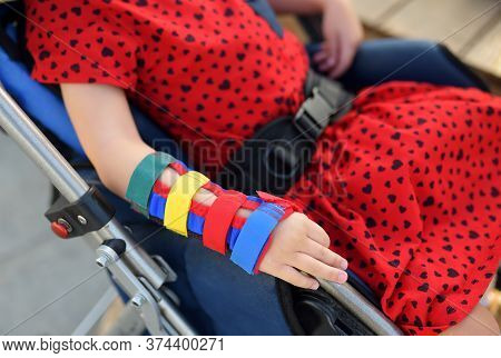 Little Disabled Girl Sitting In A Wheelchair. On Her Arms Orthosis. Child Cerebral Palsy. Inclusion.
