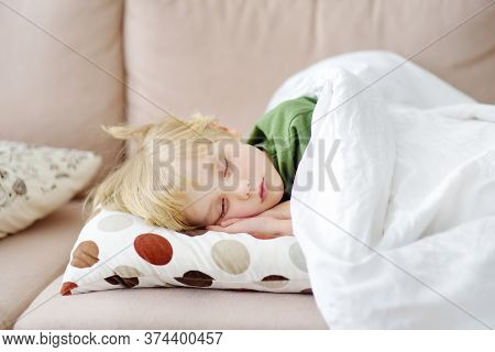 Afternoon Sleep Of Preschooler Or Elementary School Child. Tired Boy Fell Asleep On Sofa In The Afte