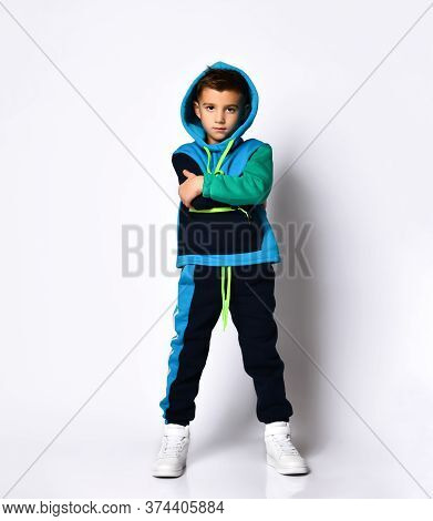 Little Brunette Child In Colorful Sport Suit And Sneakers. He Has Put His Hood On While Posing Isola