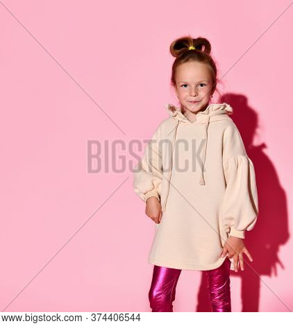 Cute Little Girl With An Updo Posing With Confident Look In Pale-pink Sweatshirt And Glossy Leggings