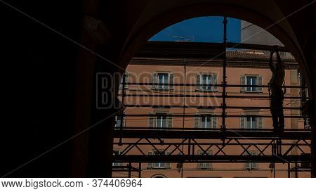 Silhouette Of Workman Standing On Scaffold In Archway In Bologna Italy