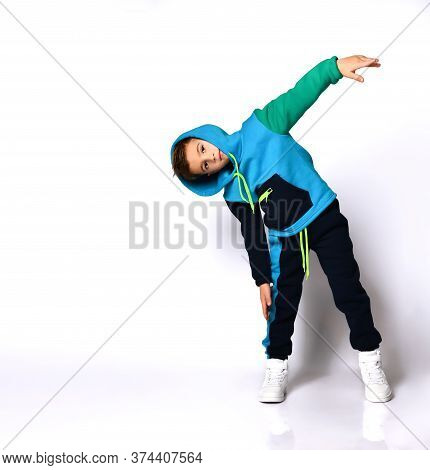 Little Brunet Boy In Colorful Sport Suit And Sneakers. He Has Put His Hood On, Performing Exercises,
