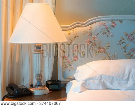 Lamp On Bedside Near Telephone, Clock And Pillow In Bedroom At Night