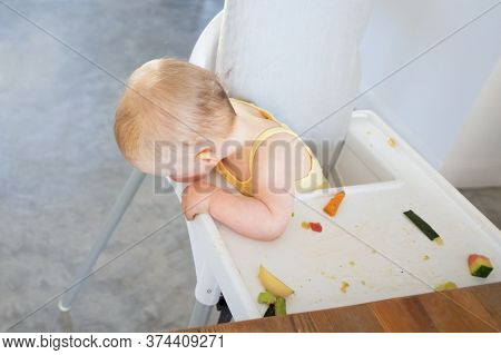 Cute Baby Girl Sitting In Highchair With Fruit Slices On Tray And Looking Down At Floor. High Angle.