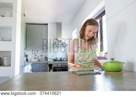 Positive Pensive Young Woman Writing Down Grocery List On Pad Screen In Her Kitchen, Using Tablet Ne