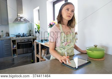 Pensive Housewife Planning Weekly Menu And Writing Grocery List In Her Kitchen, Using Tablet Near Bi
